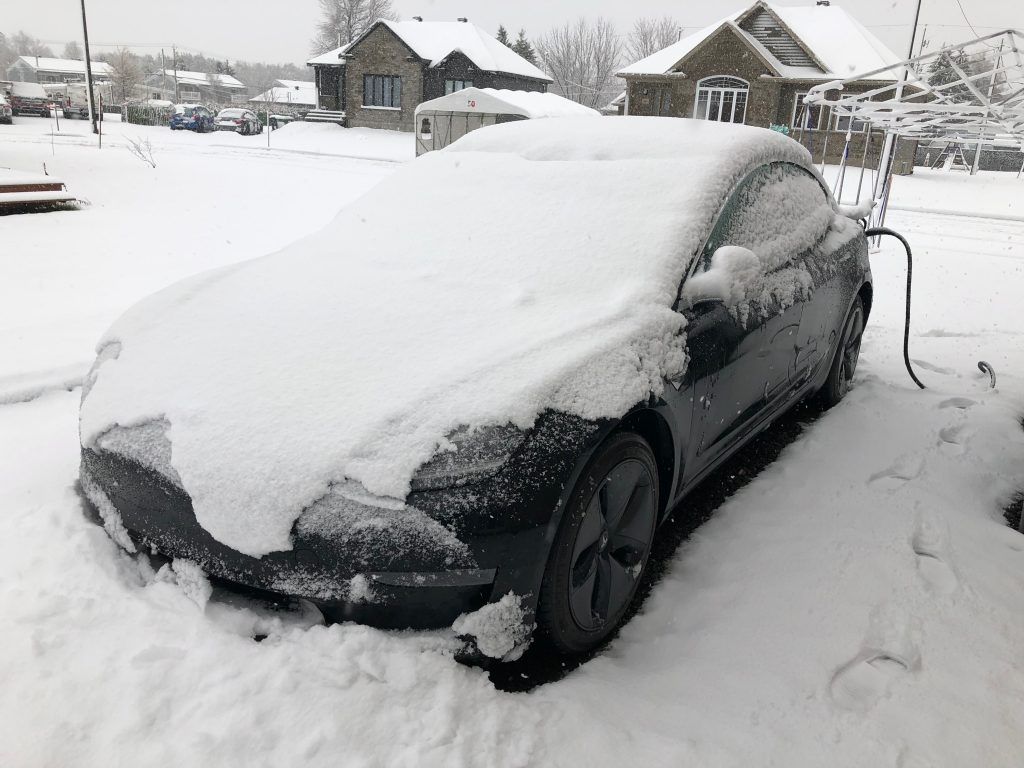 Model 3 Tesla under heavy snow